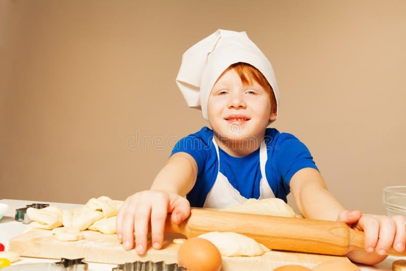 Gelukkige jonge bakker met deegrol en ruw deeg stock afbeelding
