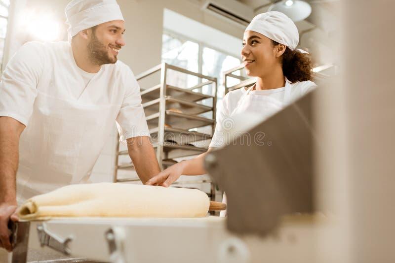 gelukkige jonge bakkers die met industriële deegrol werken royalty-vrije stock afbeeldingen