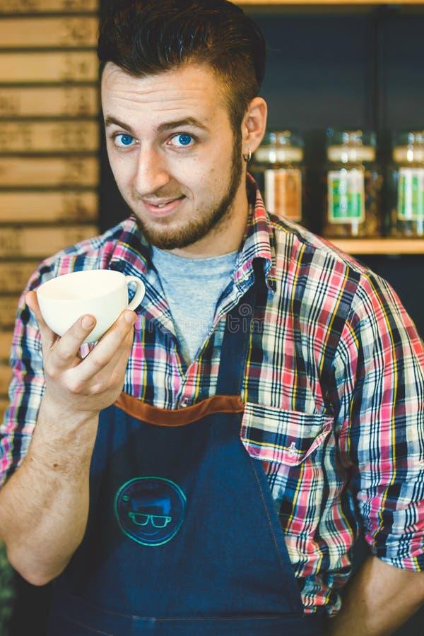 Gelukkige jonge barista die kop van koffie aanbieden gaan glimlachend bij camera stock afbeelding