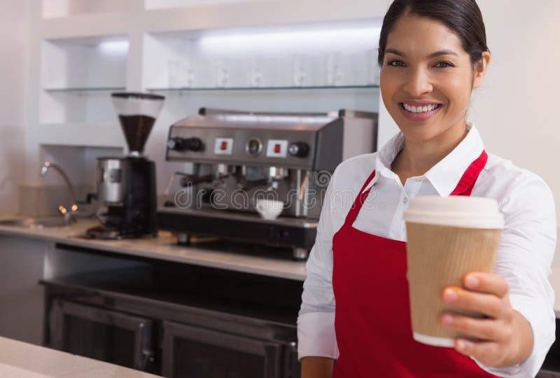 Gelukkige jonge barista die kop van koffie aanbieden gaan glimlachend bij camera stock foto's