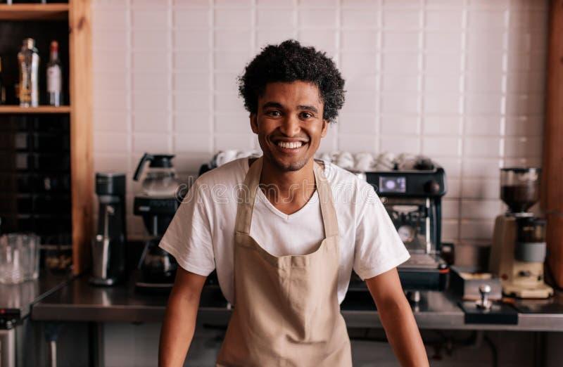 Gelukkige jonge barista die zich bij koffieteller bevinden stock afbeeldingen