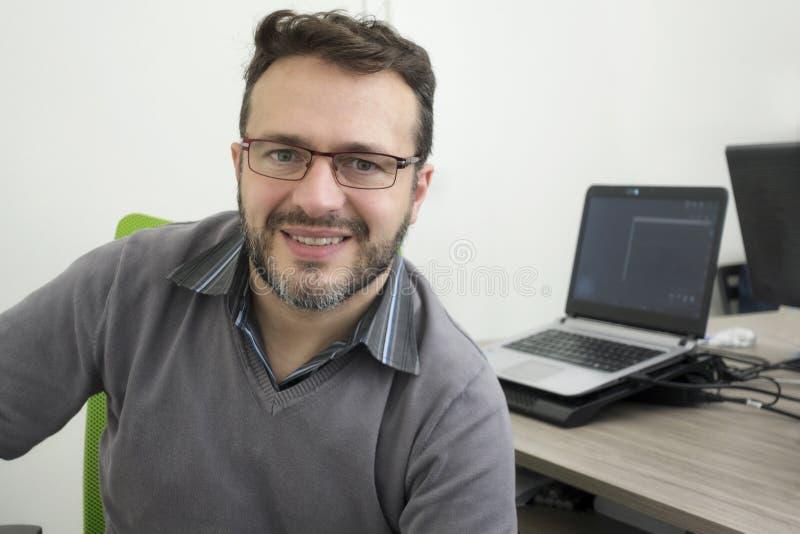 Gelukkige jonge bedrijfsmens, softwareontwikkelaar die, computertechnicus in modern bureau werken stock afbeeldingen