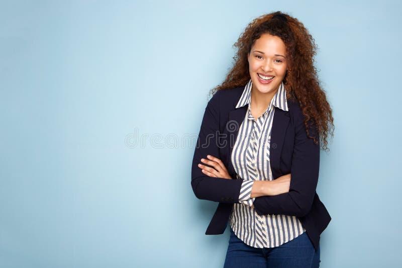 Gelukkige jonge bedrijfsvrouw die tegen blauwe achtergrond glimlachen stock fotografie
