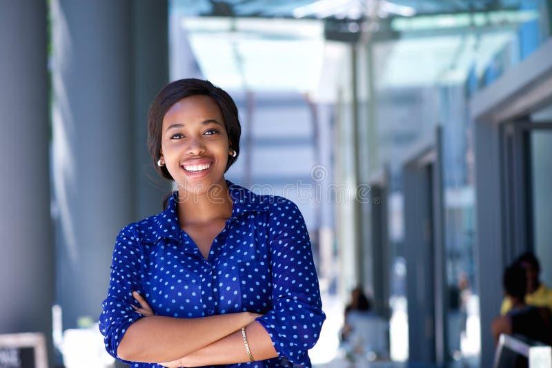 Gelukkige jonge bedrijfsvrouw die zich buiten de bureaubouw bevinden royalty-vrije stock fotografie