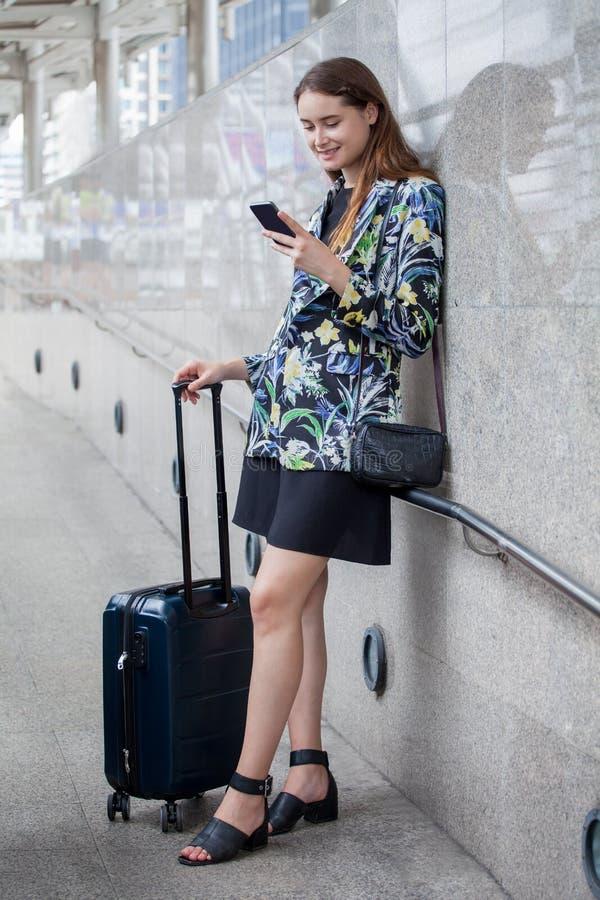 gelukkige jonge bedrijfsvrouw die zich met handbagage bevinden die mobiele telefoon met behulp van reizend meisje met koffer en s royalty-vrije stock afbeelding