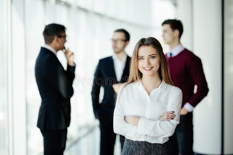 Gelukkige jonge bedrijfsvrouw die zich voor haar team in bureau bevinden royalty-vrije stock fotografie