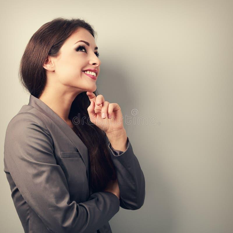 Gelukkige jonge bedrijfsvrouw in kostuum die en op leeg denken kijken royalty-vrije stock afbeelding
