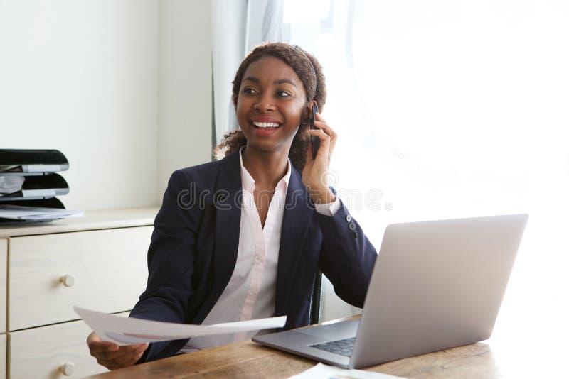 Gelukkige jonge bedrijfsvrouwenzitting bij bureau die op mobiele telefoon met een in hand document spreken stock fotografie