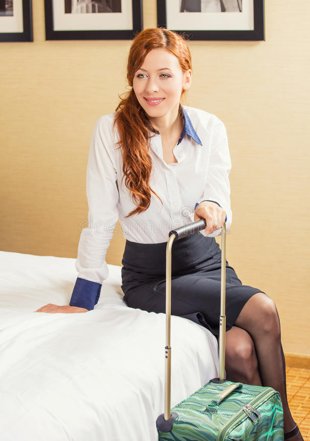 Gelukkige jonge bedrijfsvrouwenzitting op bed in hotelruimte royalty-vrije stock afbeelding