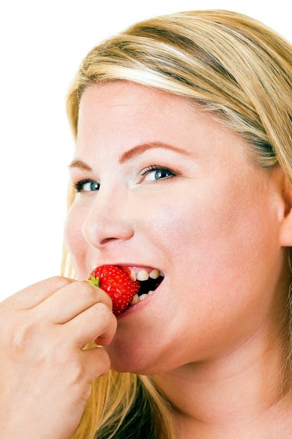 Gelukkige jonge blonde vrouw die aardbei eten royalty-vrije stock afbeelding