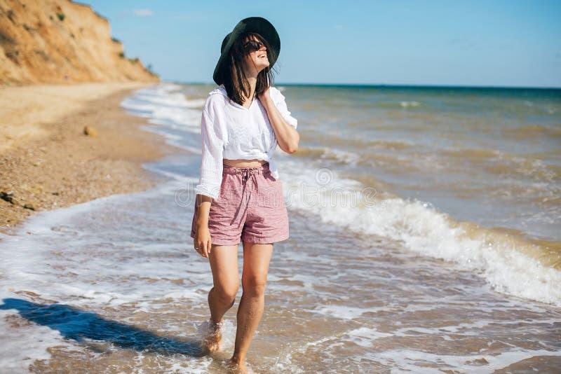 Gelukkige jonge bohovrouw die en pret in overzeese golven in zonnige warme dag op tropisch eiland lopen hebben De vakantie van de stock afbeelding