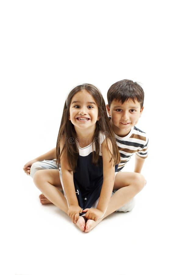Gelukkige jonge broer en zuster stellende zitting op vloer stock foto's