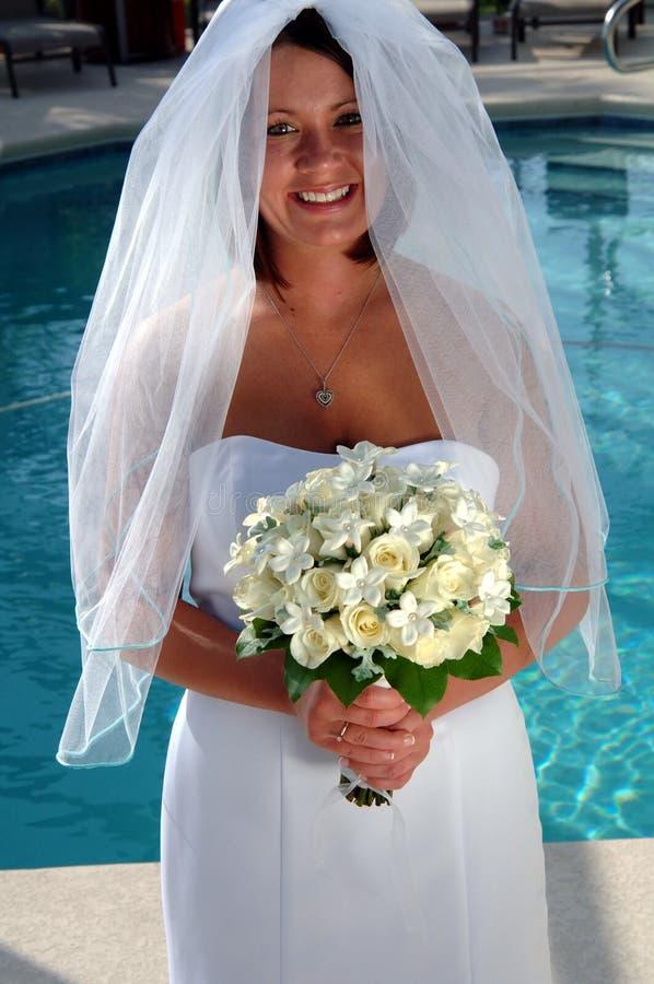 Gelukkige jonge bruid door pool royalty-vrije stock foto