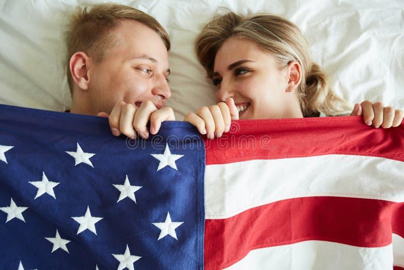 Gelukkige jonge data die met Amerikaanse vlag behandelen terwijl het liggen op bed stock foto