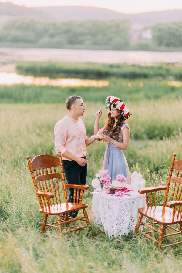 Gelukkige jonge die vrouw het voeden cake met roze bloemen aan vriend in openlucht wordt verfraaid royalty-vrije stock foto's