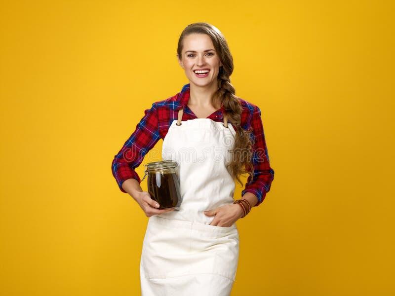 Gelukkige jonge die vrouwenlandbouwer op geel met kruik met honing wordt geïsoleerd stock foto's
