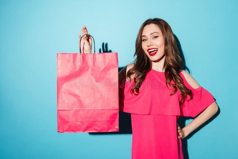 Gelukkige jonge donkerbruine dameholding het winkelen zak stock afbeelding