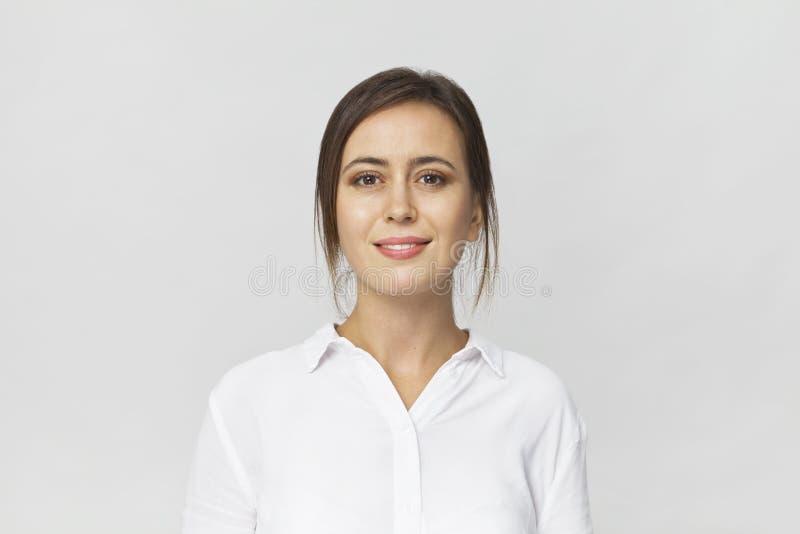 Gelukkige jonge donkerbruine vrouw die wit overhemd het glimlachen portret dragen stock foto