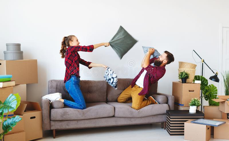 Gelukkige jonge echtpaarbewegingen aan nieuwe flat en het lachen, sprong, strijdhoofdkussens stock afbeeldingen