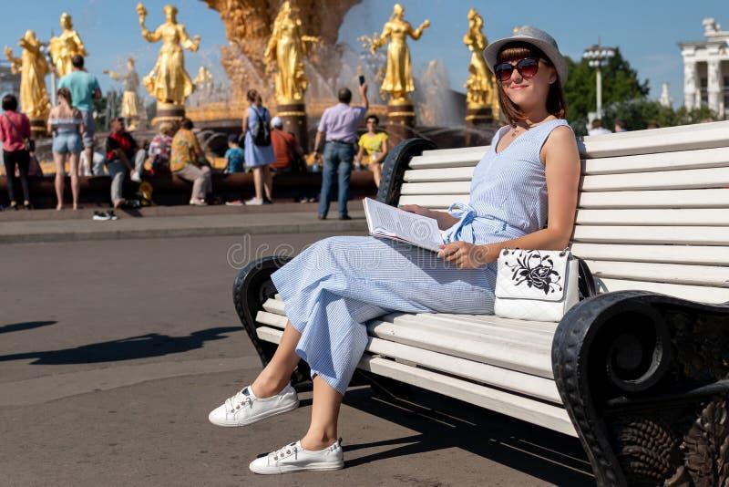 Gelukkige jonge en modieuze vrouw met hoed en boekzitting op de bank in het park royalty-vrije stock fotografie