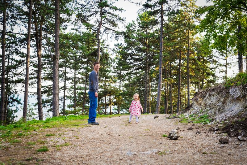 Gelukkige jonge enige vader die een gang in een park met zijn peuterdochter nemen Familie die en pret hebben lachen stock fotografie