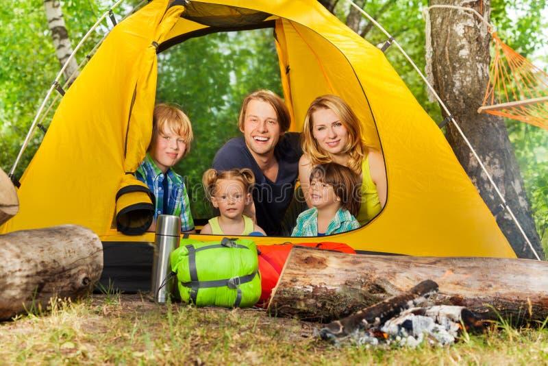 Gelukkige jonge familie die binnentent in hout ontspannen stock foto's