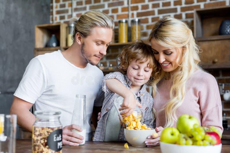 gelukkige jonge familie die cornflakes voor ontbijt eten stock afbeeldingen