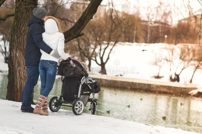 Gelukkige jonge familie die in een een een een de winterpark, mamma, papa en zoon lopen in wandelwagen royalty-vrije stock foto's