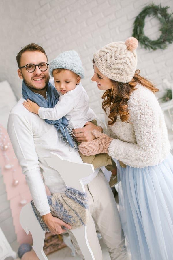 Gelukkige jonge familie die en in heldere zolderstudio glimlachen koesteren stock foto's