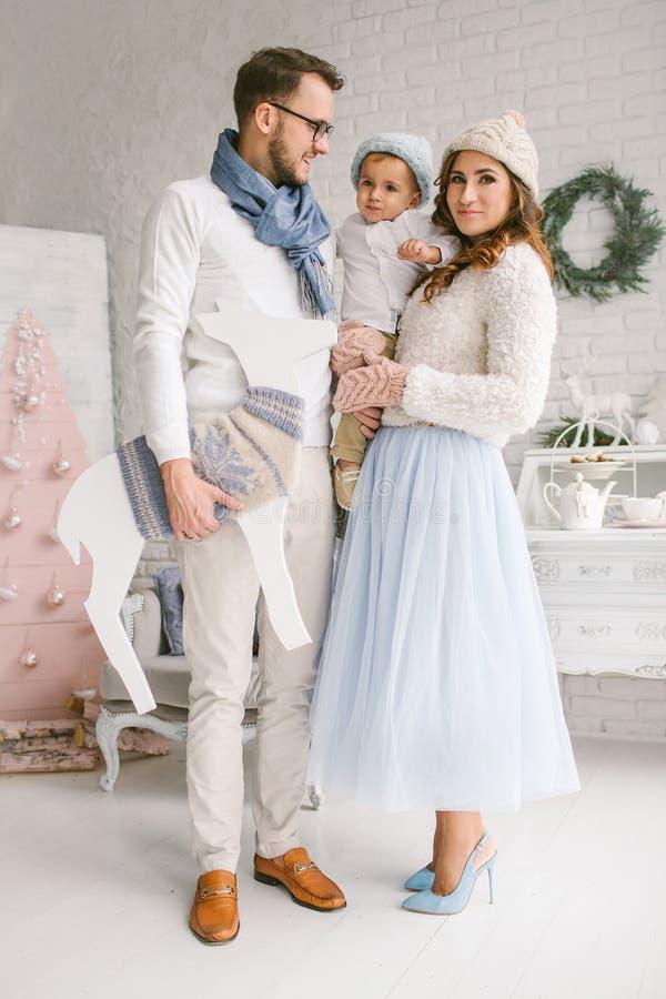 Gelukkige jonge familie die en in heldere zolderstudio glimlachen koesteren royalty-vrije stock afbeeldingen