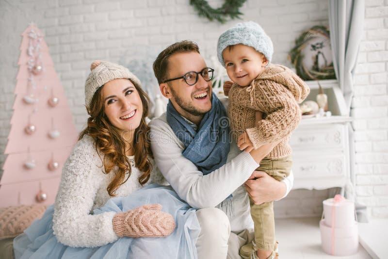Gelukkige jonge familie die en in heldere zolderstudio glimlachen koesteren stock foto
