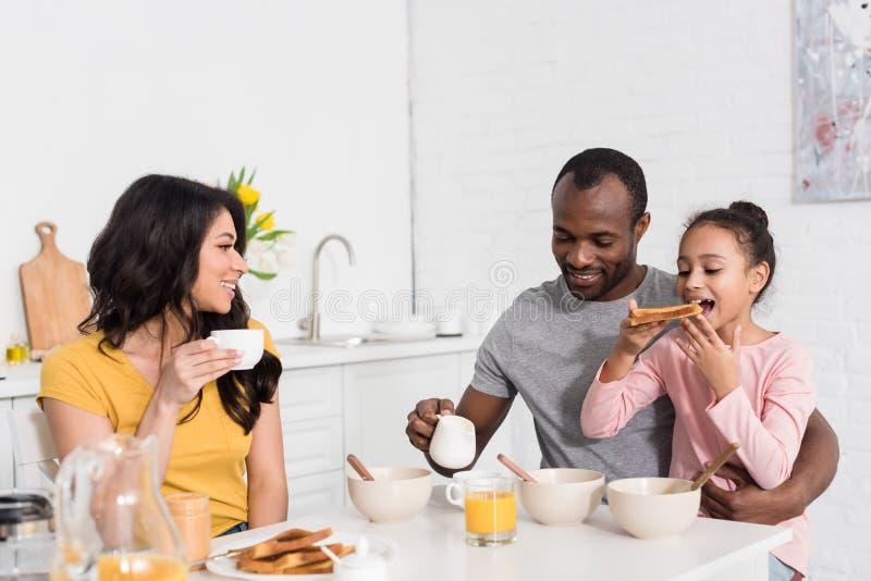 gelukkige jonge familie die gezond ontbijt hebben stock afbeelding