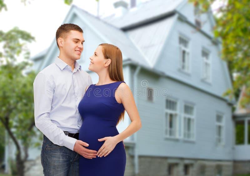 Gelukkige jonge familie die kind over huis verwachten royalty-vrije stock afbeelding