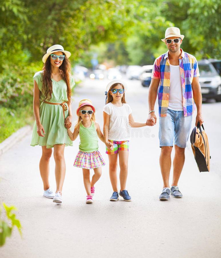 Gelukkige jonge familie die met gitaar die onbezorgde tijd doorbrengen lopen aan stock afbeelding