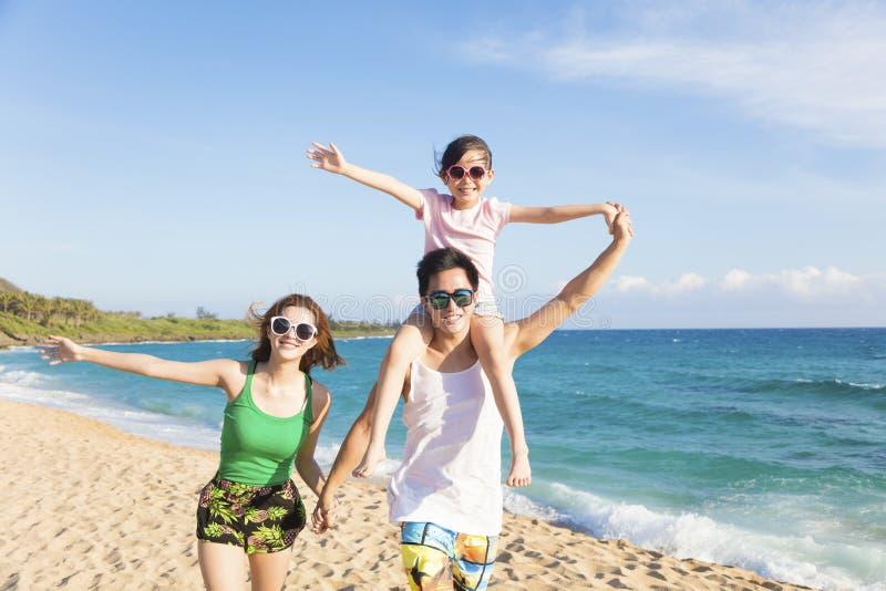 Gelukkige jonge familie die op het strand lopen royalty-vrije stock afbeelding