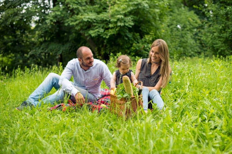 Gelukkige jonge familie die picknick in openbaar park hebben royalty-vrije stock afbeeldingen