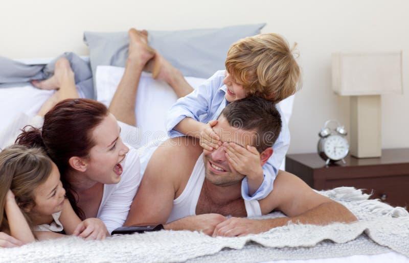 Gelukkige jonge familie die pret in bed heeft stock afbeelding