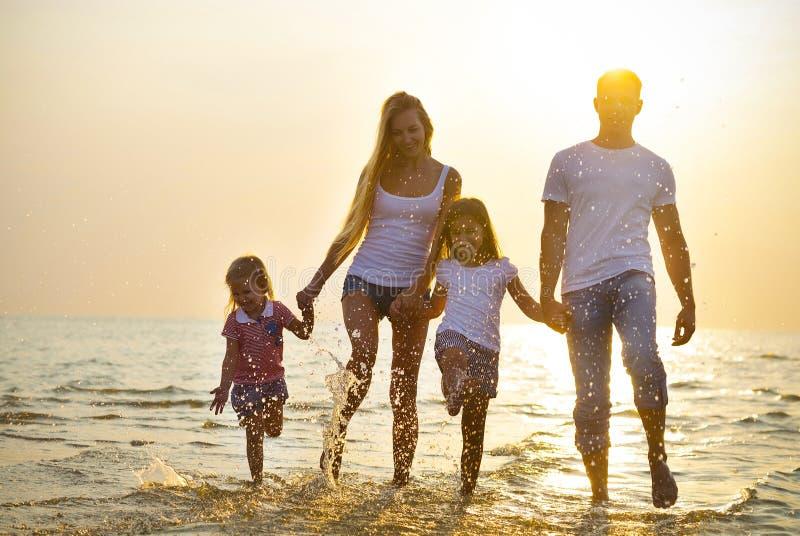 Gelukkige jonge familie die pret hebben die op strand bij zonsondergang lopen Familie stock foto