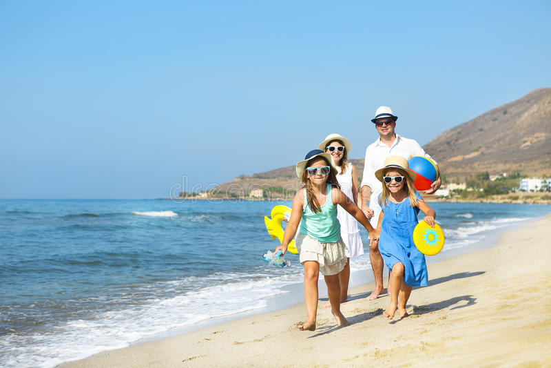 Gelukkige jonge familie die pret hebben die op strand bij zonsondergang lopen Familie stock afbeeldingen