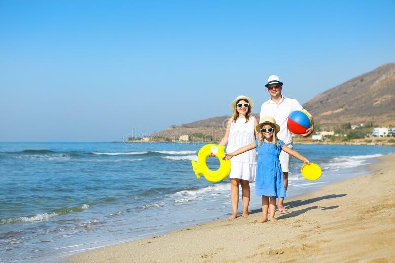 Gelukkige jonge familie die pret hebben die op strand bij zonsondergang lopen Familie stock foto's
