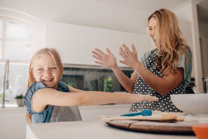 Gelukkige jonge familie die pret in keuken hebben stock foto's