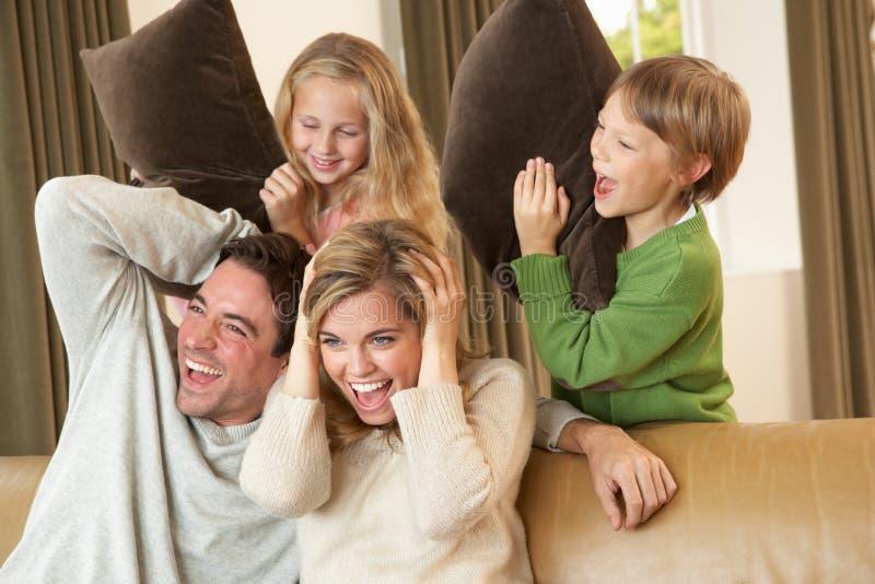 Gelukkige jonge familie die pret met hoofdkussens op bank heeft stock foto
