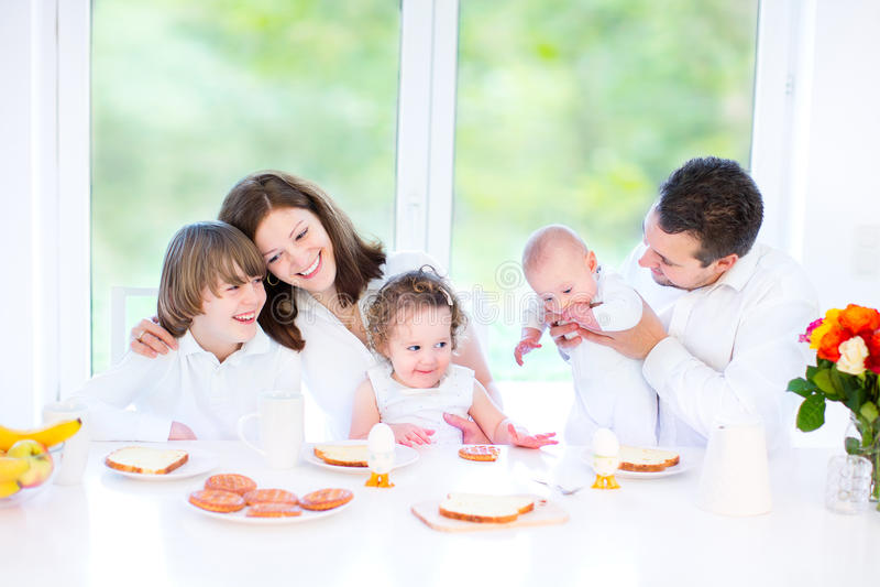 Gelukkige jonge familie die pretontbijt hebben stock afbeelding