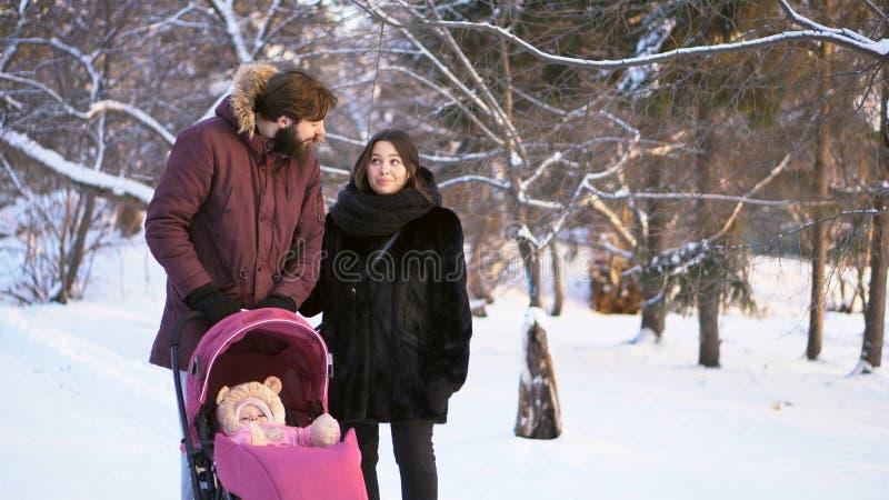 Gelukkige, jonge familie in een de winterpark lopen, mamma, papa en baby die in roze wandelwagen Mens de vinger richten en ouders royalty-vrije stock afbeeldingen