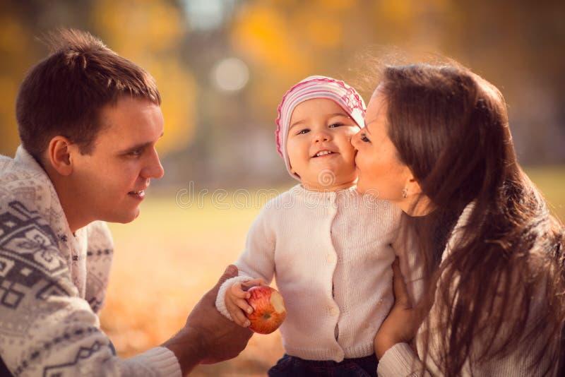 Gelukkige jonge familie het besteden tijd openlucht in het de herfstpark stock fotografie