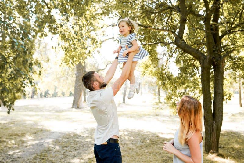 Gelukkige jonge familie het besteden tijd samen buiten in groene aard Ouders, kinderjaren, kind, zorg, dochter, vader, moeder stock fotografie