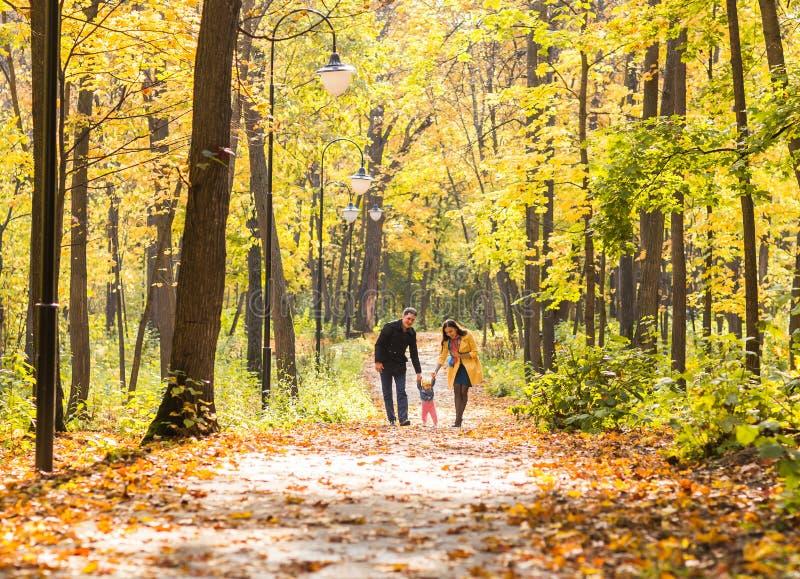 Gelukkige jonge familie in het de herfstpark in openlucht op een zonnige dag De moeder, de vader en hun klein babymeisje lopen bi royalty-vrije stock foto's