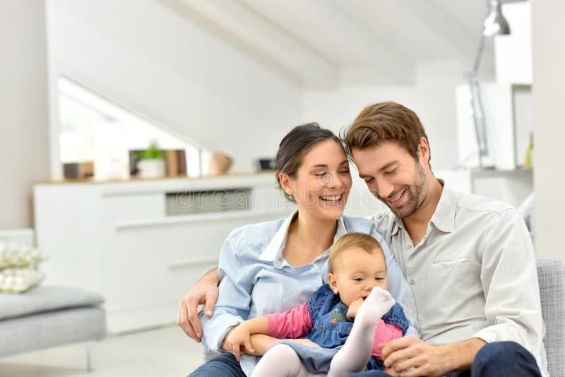 Gelukkige jonge familie met baby thuis royalty-vrije stock afbeelding