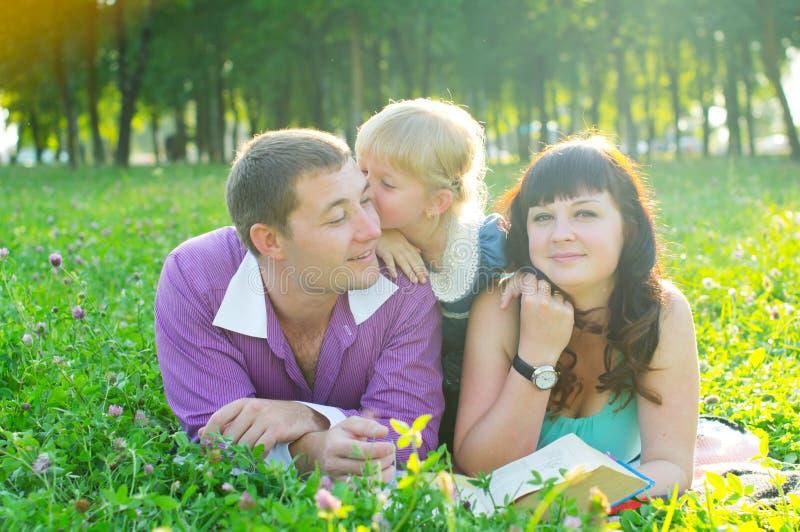 Gelukkige jonge familie met een kind die op het gras liggen royalty-vrije stock foto