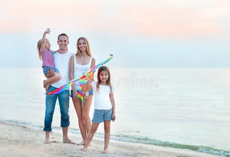 Gelukkige jonge familie met het vliegen van een vlieger op het strand royalty-vrije stock foto's